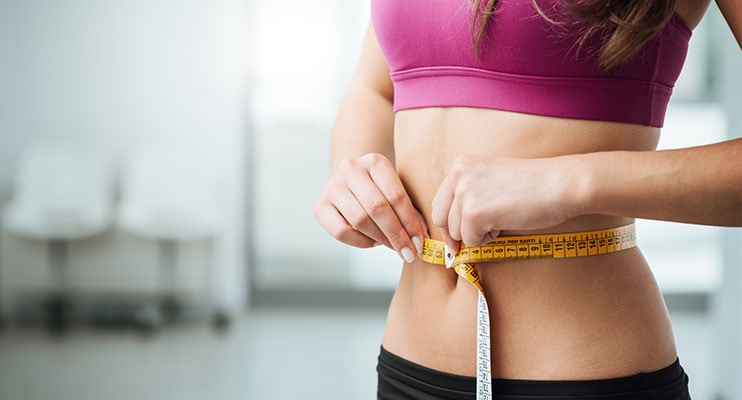 Woman In Pink Tanktop Measuring Her Weight Loss