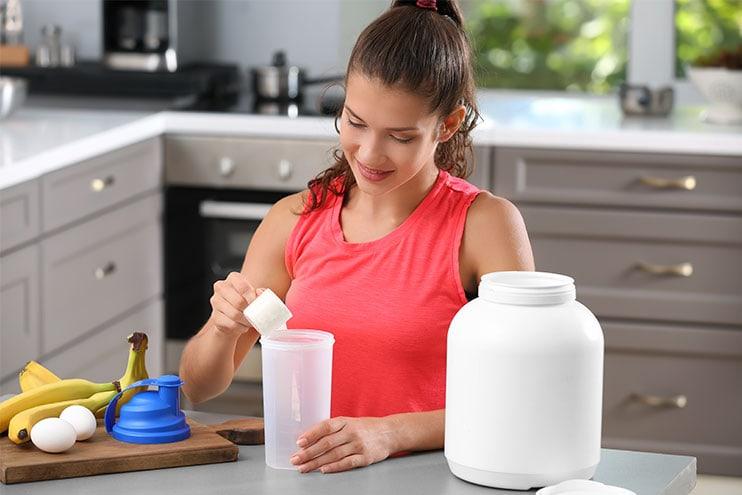 Млада жена, която прави протеинов шейк в кухнята