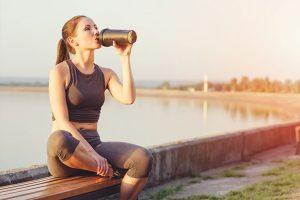 युवा महिला बेंच पर बैठकर झील के किनारे पीने के प्रोटीन शेक