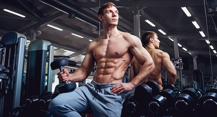 Bodybuilder Posing And Holding A Dumbbell