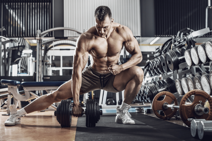 focused male bodybuilder lifting a heavy dumbbell in the gym