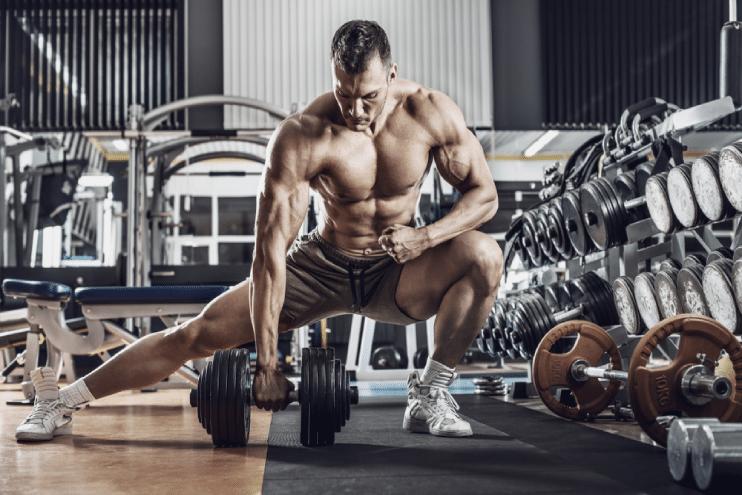 binaragawan pria fokus mengangkat halter berat di gym