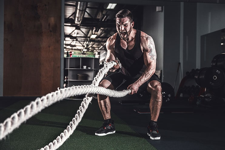 Muscular Guy Using Battle Ropes In The Gym