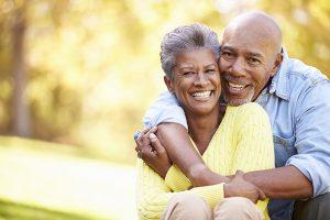 बुजुर्ग युगल गले लगाना और मुस्कुराते हुए
