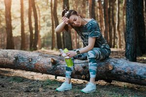 Girl Sitting On Log Recovering After Workout