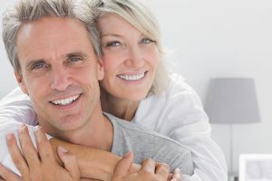 Healthy Man Smiling While His Wife Hugs Him