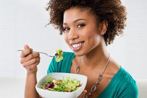 स्वस्थ महिला एक सलाद खा रही है