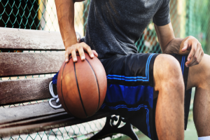 баскетболист сидит на скамейке, держа руку на мяч