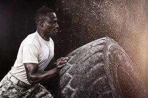 एक बड़े ट्रक टायर पर मजबूत आदमी Flipping