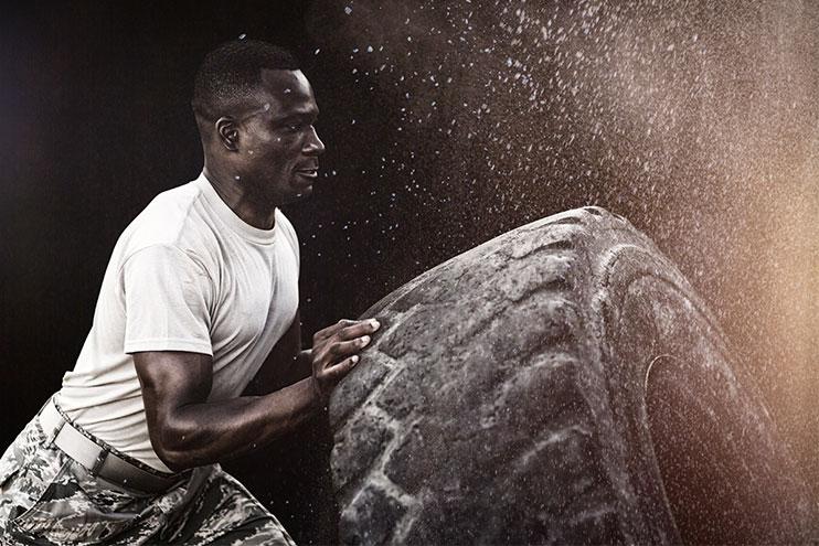 Силен човек, прелистващ голяма гума на камион