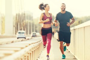 Young Couple Jogging Together And Smiling