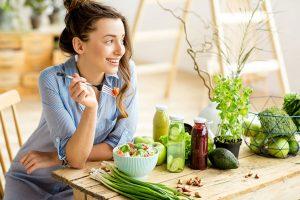 युवा महिला सब्जी खा रही है