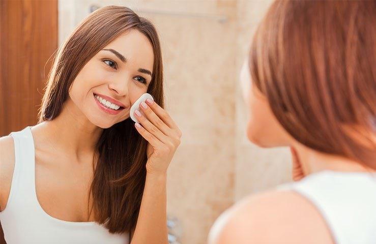거울에 그녀의 피부를 치료하는 젊은 여자
