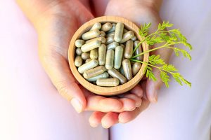 Female Hands Holding A Bowl Full Of Herbal Supplements
