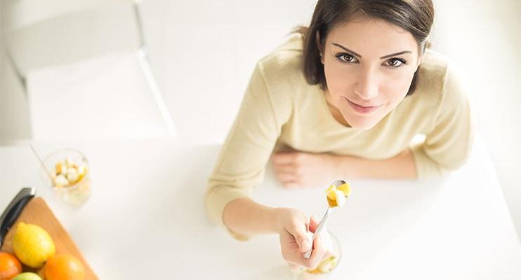 زن در حال جستجو در دوربین در حالی که نگه داشتن یک قاشق کامل از ویتامین ها
