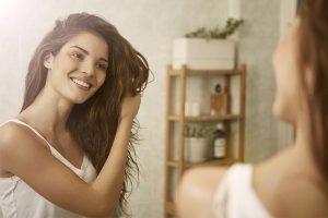 भूरे बालों वाली महिला दर्पण में उसके स्वस्थ बालों की जाँच