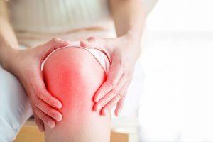Ang Tao na Naghahawak ng Kanyang Mga Kamay Niya sa Kanyang Inflamed Knee