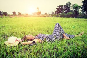 Smilende kvinne legger seg ned i gresset under en skinnende sol
