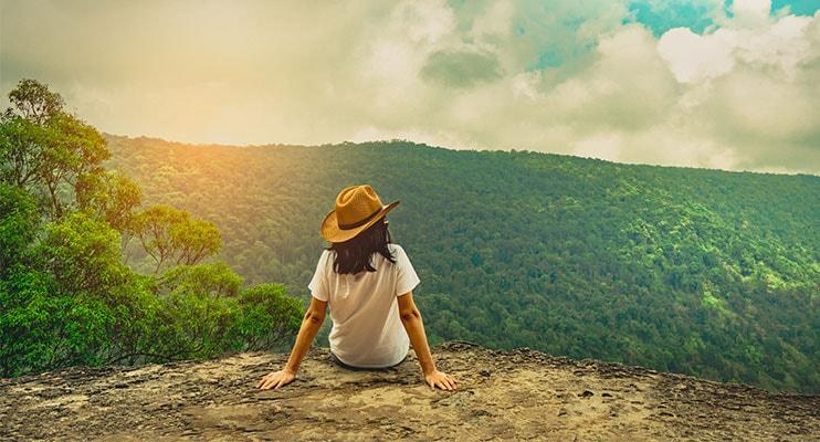 Жена, седнала на скала над планински терен