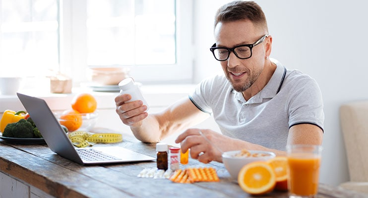 Guy With Glasses Sitting In Front Of Laptop Reading A Supplement Label