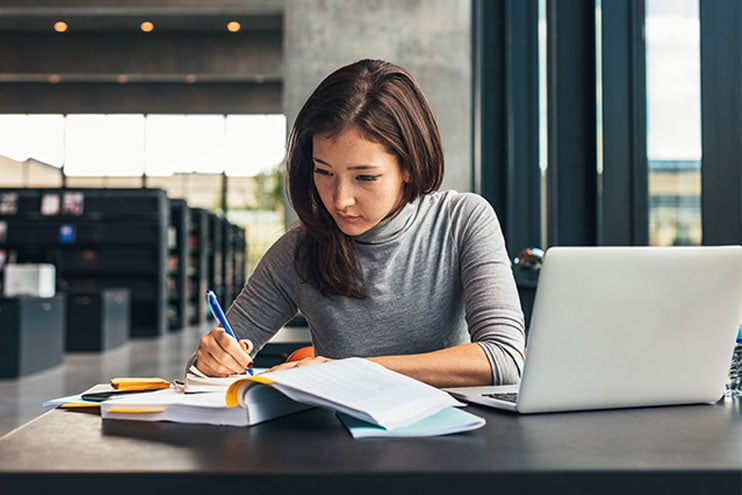 Young Woman Sitting In Library Studying With Book And Laptop