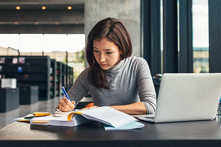 पुस्तकालय और लैपटॉप के साथ अध्ययन में लाइब्रेरी में बैठी युवा महिला