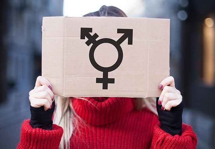 Chica en suéter rojo con signo de transgénero