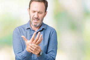 पुराने आदमी गठिया से अपने हाथ में दर्द महसूस कर रहा है