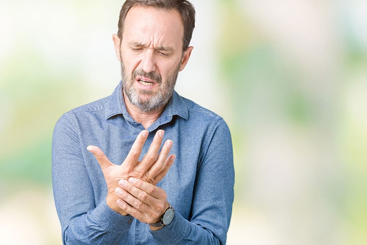 Homem mais velho, sentindo a dor na mão de artrite
