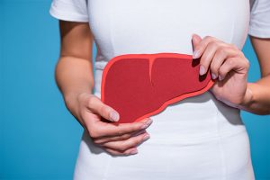 Woman Holding Paper Crafted Liver In Hands On Blue Background