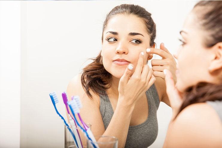 Mujer joven mirando una espinilla en el espejo
