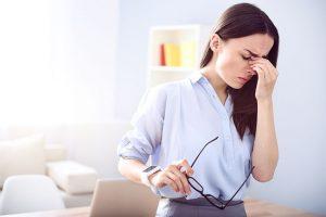 एक माइग्रेन से पीड़ित उसकी नाक का पुल पकड़े युवा महिला